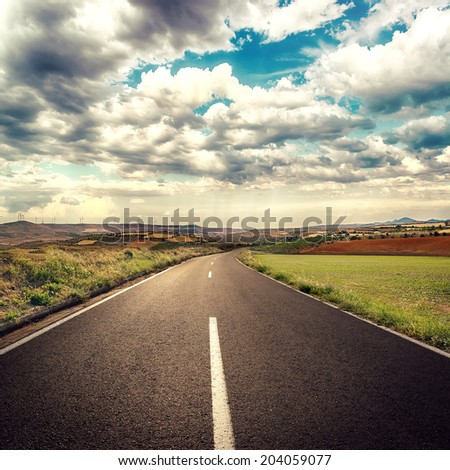 Asphalt road through green field over white cloudscape background.  - stock photo