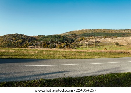 Asphalt road through the green field and clean blue sky in autumn day.  - stock photo
