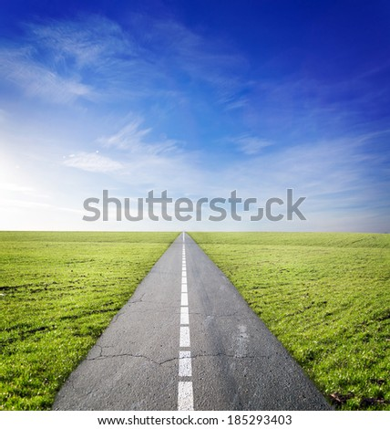 asphalt road through the green field and clouds on blue sky in summer day - stock photo