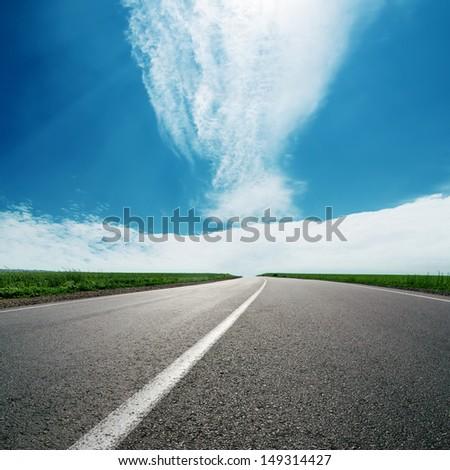asphalt road to cloudy horizon in blue sky - stock photo