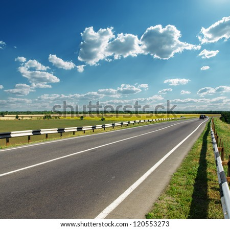 asphalt road to horizon in cloudy sky - stock photo