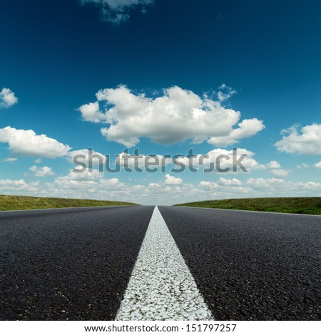 asphalt road to horizon in deep blue cloudy sky - stock photo