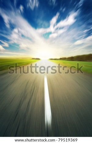 asphalt road under blue sky speed blur background - stock photo