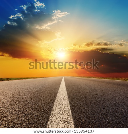 asphalt road under sunset with clouds - stock photo