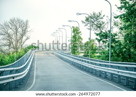 Asphalt road with green trees and sky - stock photo