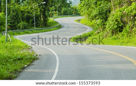 Asphalt road with tropical forest - stock photo