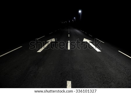 Asphalt road with white arrow signs at night - stock photo