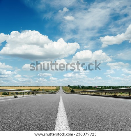 asphalt road with white line on center close up under cloudy sky - stock photo