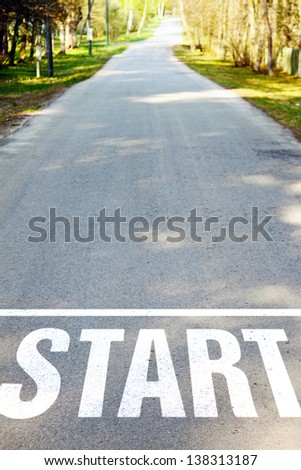 asphalt road with white start sign - stock photo