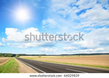 Asphalt rural road to green hills.  Belarus - stock photo