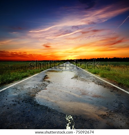Asphalt the old road into a field and puddles - stock photo