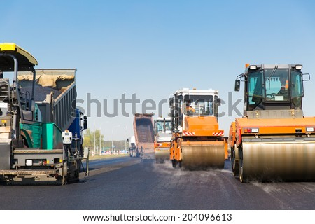 Asphalting construction works with commercial repair equipment road crews - stock photo