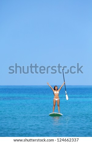 Aspirational beach lifestyle woman on paddleboard enjoying summer holidays vacation in bikini on hawaii. Beautiful mixed race girl on hawaiian paddleboard with arms raised in happiness. - stock photo