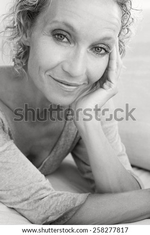 Aspirational black and white beauty portrait of an attractive mature healthy woman laying down on a white sofa at home, smiling and relaxing indoors. Home living and well being lifestyle. - stock photo