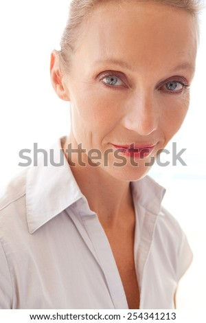 Aspirational close up portrait of professional mature business woman smiling to the camera while against a bright white light background wall, indoors. Beautiful senior business woman smartly dressed. - stock photo