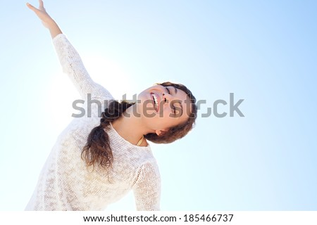 Aspirational energetic portrait of an attractive young woman being playful and enjoying life with her arms stretched against a sunny blue sky with the sun rays filtering in. Joyful lifestyle. - stock photo