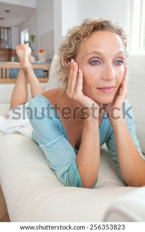 Aspirational home portrait of an attractive mature healthy woman laying on a white sofa at home, thoughtful and relaxing indoors. Home living and well being lifestyle, aging well middle age woman. - stock photo