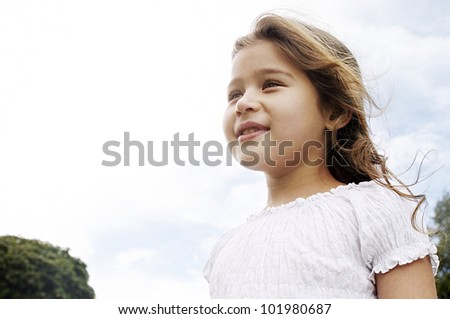 Aspirational portrait of a young girl smiling in the park with her hair blowing in the wind. - stock photo