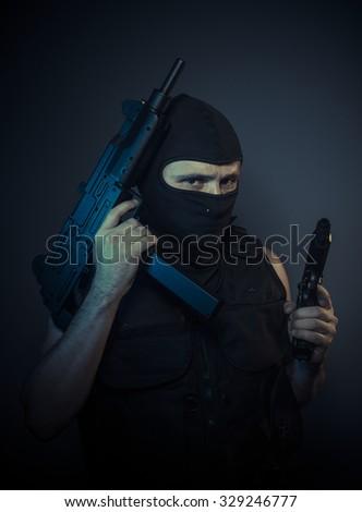 Assassin, terrorist carrying a machine gun and balaclava - stock photo