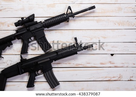 Assault automatic rifle on white wooden table - stock photo