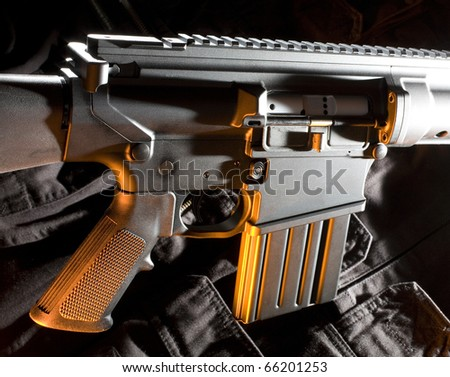 Assault rifle that has an orange gel applied to it - stock photo
