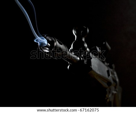 Assault rifle with smoke coming from its barrel in the dark - stock photo