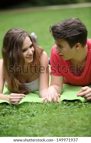 Assectionate teenage couple on a date lying holding hands on a rug in the park chatting and looking into each others eyes - stock photo