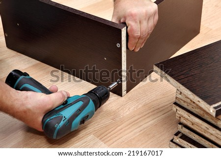 Assembling furniture from chipboard, using a cordless screwdriver, close up. - stock photo
