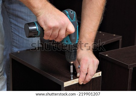 Assembling furniture, Hands of a carpenter with a electric Cordless screwdriver, tighten the screw in drawers of chipboard. - stock photo
