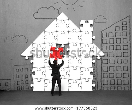 Assembling house shape puzzles on concrete wall with doodles - stock photo