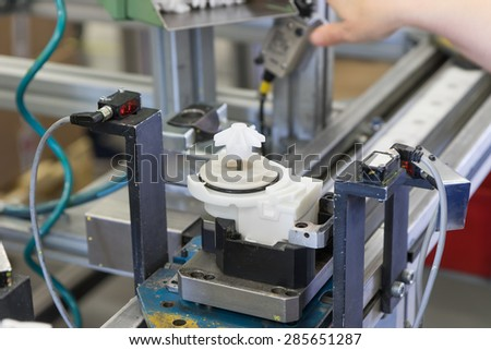 Assembly line of plastic components. Blurred hand of the worker is in the upper side of the photo. - stock photo