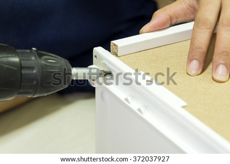 Assembly the furniture by using the screw driver - stock photo