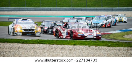 ASSEN, NETHERLANDS - OCTOBER 19, 2014: Competitors in the supercar challenge following eachother through a chicane on TT Circuit Assen - stock photo