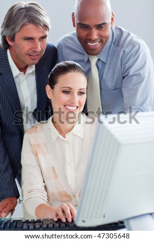 Assertive business people working at a computer in the office - stock photo