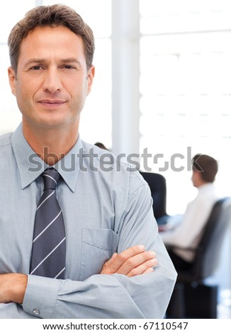 Assertive businessman standing in front of his team while working at a table in the background - stock photo
