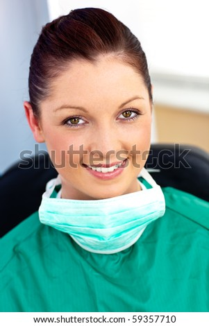 Assertive female doctor with scrubs sitting in her office on her armchair - stock photo