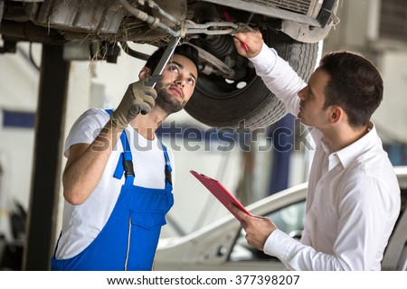 assessor and repair man examine to the car damage - stock photo