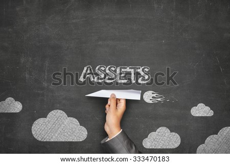 Assets concept on black blackboard with businessman hand holding paper plane - stock photo