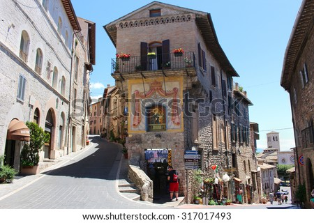 ASSISI, ITALY - JUNE 24, 2014: Hilly Street in the town of Assisi Italy showing souvenir shops for tourists  - stock photo