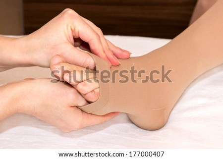 Assistance by putting on DVT stockings - stock photo