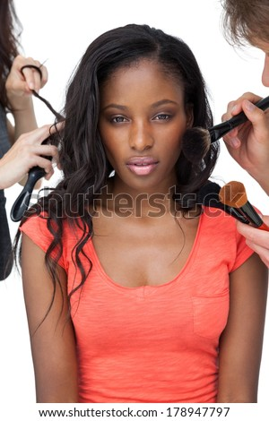 Assistants applying make-up to a female model over white background - stock photo