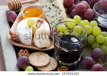 Assorted appetizers to wine - cheeses, fresh grapes, crackers and honey, horizontal, close-up - stock photo