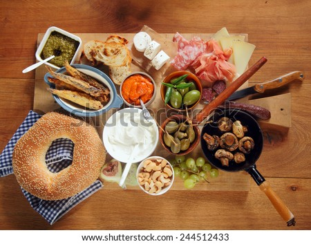 Assorted Appetizing Tapas on Wooden Board on Top of Wooden Table. Emphasizing Doughnut, Cheese, Meats and Vegetables. - stock photo