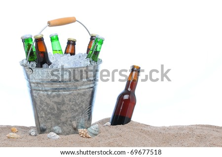 Assorted beer bottles in a bucket of ice in the sand isolated on white. One beer bottle without a cap is by itself stuck in the sand next to the pail. - stock photo