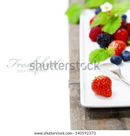 Assorted berries on a plate (with easy removable sample text) - stock photo