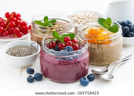 assorted breakfast of chia seeds and fruits in jars on white table, closeup - stock photo