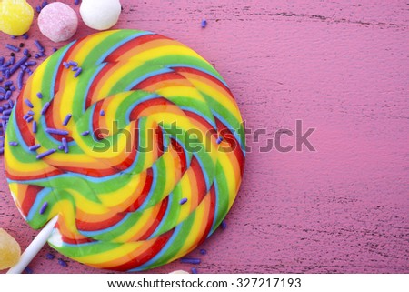 Assorted candy and rainbow lollipop on pink wood rustic table background with copy space.  - stock photo