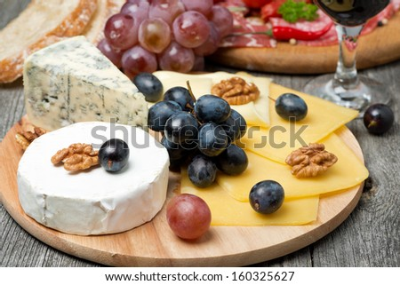 Assorted cheese, grapes, wine and sausages on wooden board - stock photo