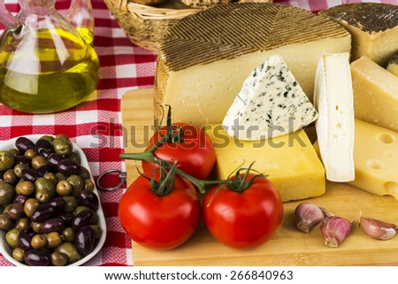 Assorted cheese olives tomatoes and other ingredients typical of the Mediterranean diet - stock photo