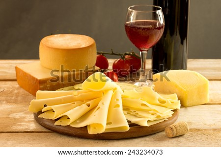 assorted cheese with red wine on a rustic table - stock photo